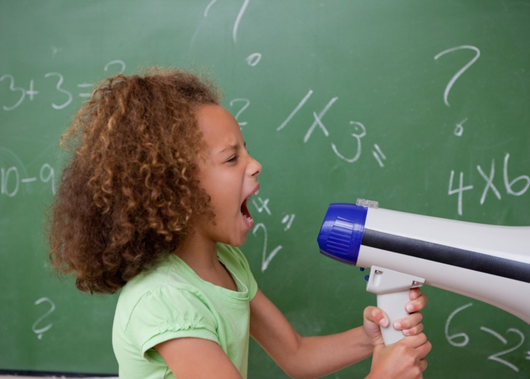 Girl in a classroom screaming into a megaphone